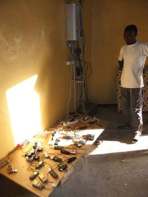 Villagers charge their cell phones using solar power